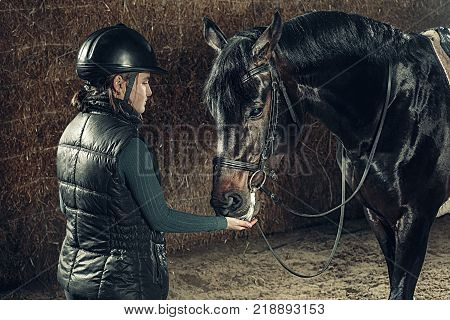 Image of happy female standing near purebred horse outdoors
