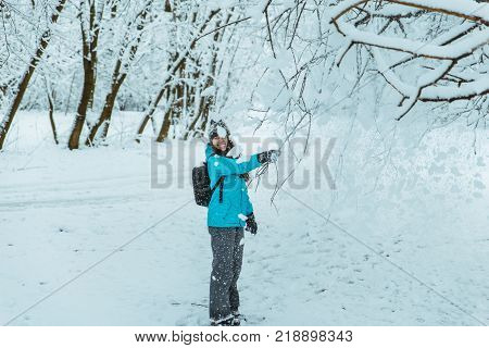 young woman hold brench covered by snow