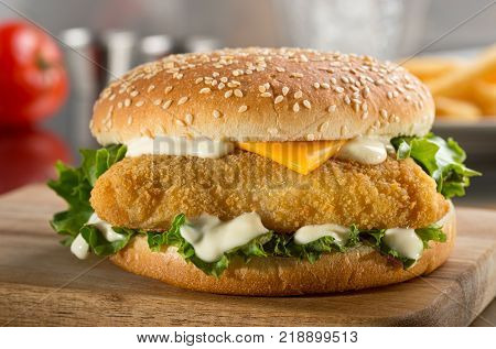 A delicious crispy fish burger with cheese lettuce and mayonnaise.