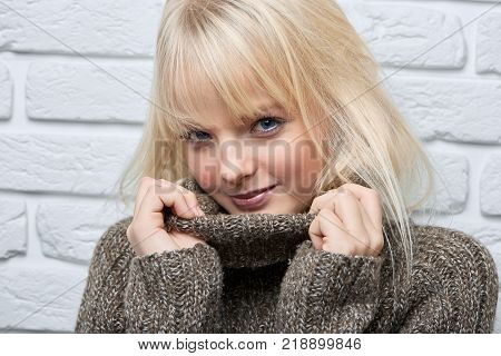 CLose up portrait of a beautiful flirtatious playful young woman smiling to the camera wearing cozy warm winter sweater positivity beauty seduction enjoyment vitality concept.