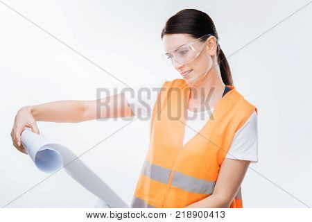 Genius blueprint. Calm confident female  engineer regarding at  blueprint  and wearing glasses  while posing on the white  background