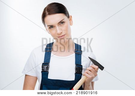 Lets destroy. Earnest concentrated female worker taking hammer and looking at the camera  while posing on the isolated background