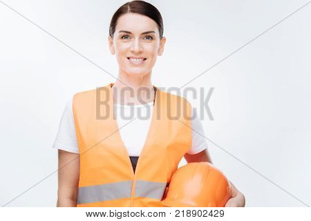 Building process. Pretty energetic female worker  wearing safety vest while standing on the white background and smiling