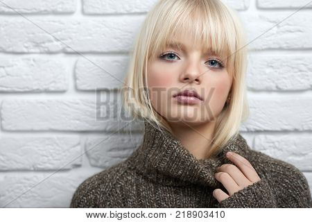 Close up of a young sexy blonde haired woman posing sensually wearing woolen sweater leaning on a brick wall copyspace seduction femininity beauty fashion seasonal coziness.