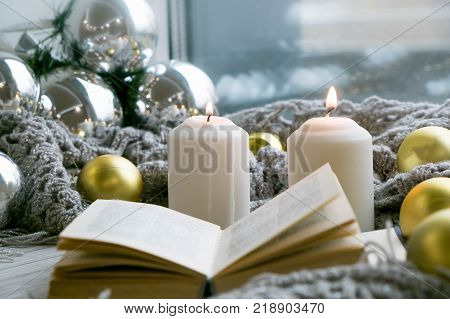 Interior of room with cozy window sill, cup of tea, books, candels, homely comfy rest concept