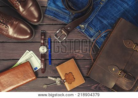 Top view, men's fashion personal belongings and accessories with space on a dark wooden background. Leather bag, shoes, watch, jeans, belt.