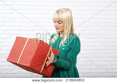 Horizontal portrait of a young blonde haired woman wearing green dress looking at the big present she is holding copyspace curiosity surprise x-mas Christmas New Year emotions.