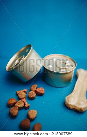Nutritious meal for your little buddy. Tin cans of pet food and a chew bone on a bright one-color blue background. Pet care and veterinary concept. Spase for your text or image.