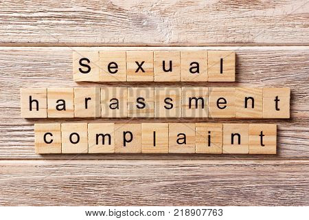 Sexual harassment complaint word written on wood block. Sexual harassment complaint text on table concept.