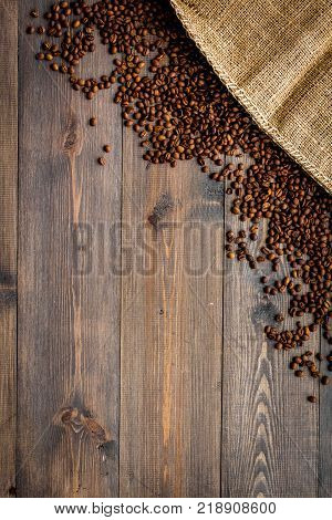 Roasted beans near canvas on dark wooden table top view copyspace. Coffee background