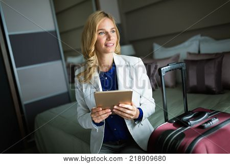 Young attractive businesswoman in hotel room holding baggage