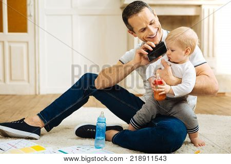 Hello. Cheerful emotional positive father looking happy while giving a smartphone to a calm child and persuading him to have a phone talk with loving relatives