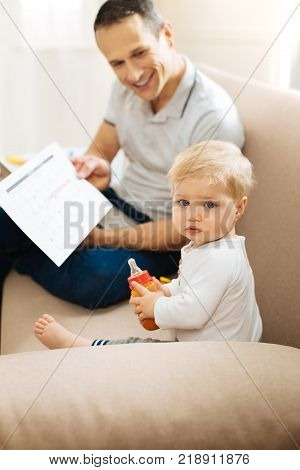 Attentive child. Calm quiet little baby looking serious while sitting on a soft comfortable sofa with a kind loving cheerful father and holding a bottle with tasty food