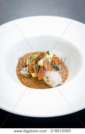 gourmet fusion cuisine stuffed squid with asian pickled vegetables in pumpkin curry sauce