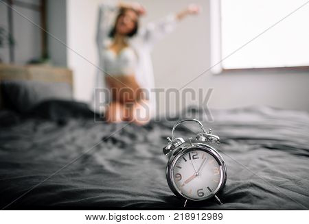 pretty happy girl waking up in the morning and switching off the alarm clock. Young beautiful, woman waking in the morning up fully rested