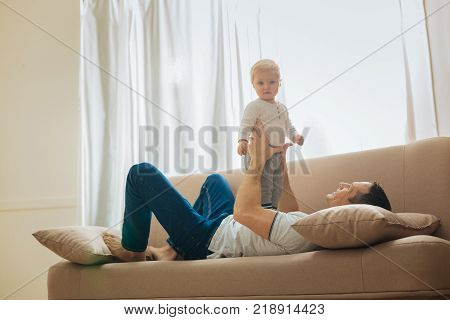 Relax. Kind loving father relaxing on a soft big sofa and looking at his adorable little child standing on his tummy and feeling curious
