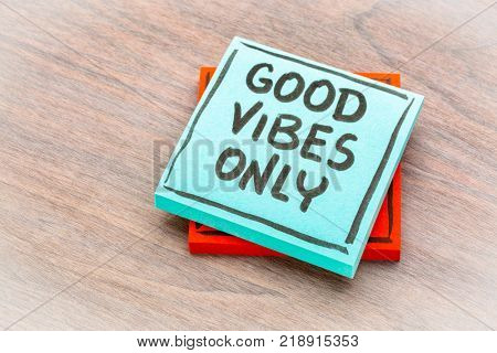 Good vibes only reminder - handwriting on a sticky note against grained wood