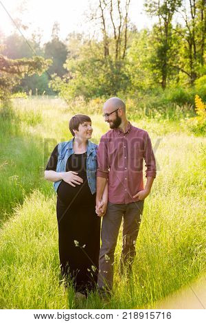 Man and a pregnant woman in a field in Oregon while the girl is in her third trimester. The couple is married and this husband and wife are expecting their first child.