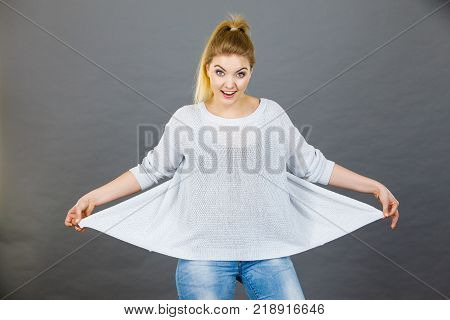 Woman wearing too big jumper not fitting after weight loss. Grey background