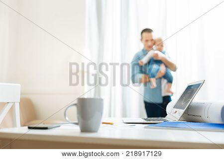 Dear person. Emotional sensible father feeling special connection between him and his little baby while holding this important little person in his arms