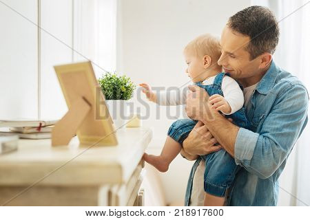 Touching things. Smart responsible kind father showing his curious interested baby many lovely items on the fireplace while making a small excursion in a house