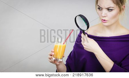 Blonde woman holding magnifying glass investigating and looking closely at glass with orange juice.