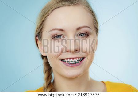 Dentist and orthodontist concept. Young woman teen girl smiling showing teeth with braces on blue