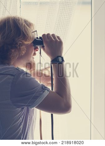 Funny guy looking through window using binoculars to peek at the neighbors.