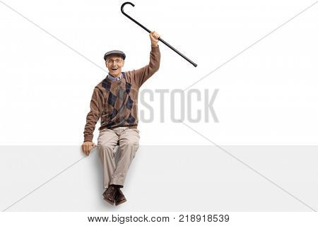 Joyful elderly man with a cane sitting on a panel isolated on white background