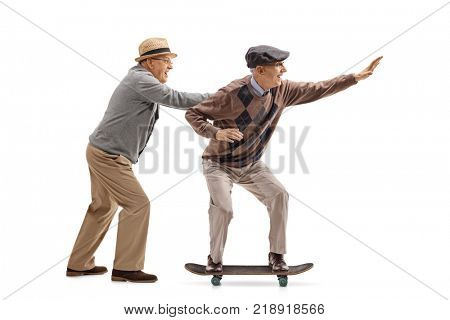 Full length profile shot of a senior pushing another senior on a skateboard isolated on white background