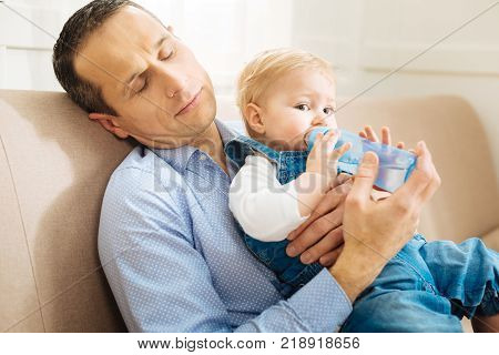 Exhausted parent. Cute little pleasant baby feeling calm and drinking water from the bottle while his tired father falling asleep on the sofa