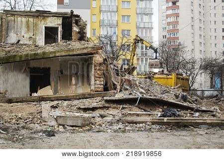 The bulldozer demolished the old building on the background of new housing