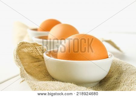 Raw brown chicken eggs in glass bowls on a white wooden table. Ingredients for cooking