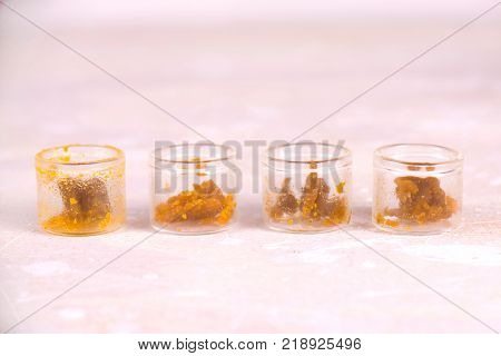 Macro detail of assorted marijuana extraction concentrate aka wax crumble on jars isolated on white background