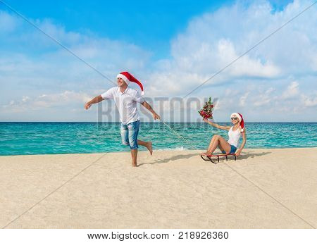 Cheerful smiling couple in red Santa hats walking at tropical ocean sandy beach with sleds and decorated fir tree. Happy New Year and Merry Christmas vacation in hot countries concept.