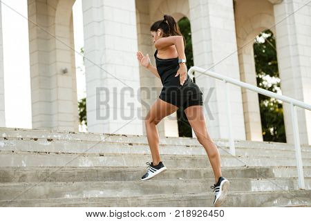 Portrait of a fitness woman in earphones running up the stairs outdoors