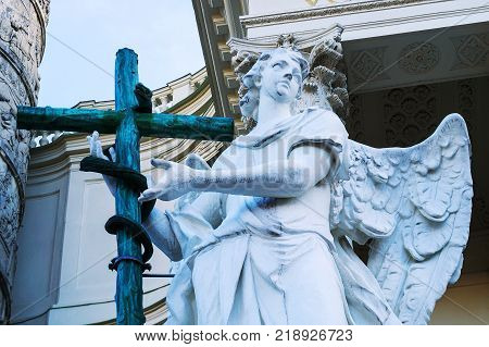 Angel statue with a cross and snake in front of Karlskirche eng. St. Charles' Church Vienna Austria