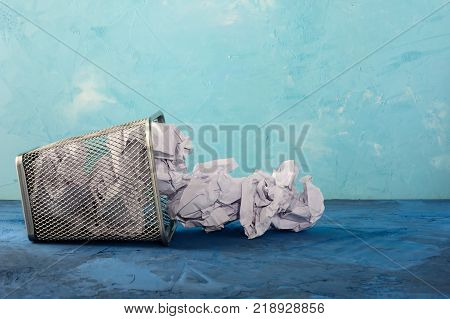 A fallen trash can for paper. Scattered paper lumps. Beautiful unusual background with place for text. Empty bin.
