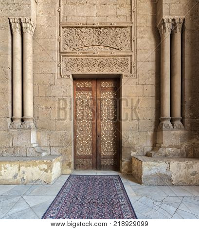 External old decorated bricks stone wall with arabesque decorated wooden door framed by stone ornate cylindrical columns leading to al Rifai Mosque Old Cairo Egypt