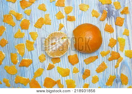 Rustic background. Exotic fruits. An overhead photo of tangerine without peel. Peeled juicy tangerine on the wooden blue table and a lot of pieces of orange peel. Rustic background