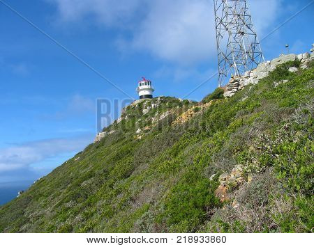 THE CAPE POINT LIGHT HOUSE STANDS ON TOP OF A HILL