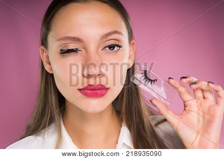 The young girl on a pink background puts false eyelashes