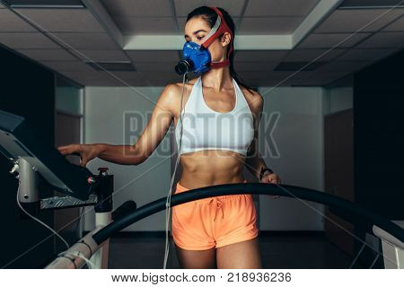 Performance testing in sorts lab. Female runner with mask on treadmill in sports science laboratory. Athlete measuring performance and oxygen consumption.