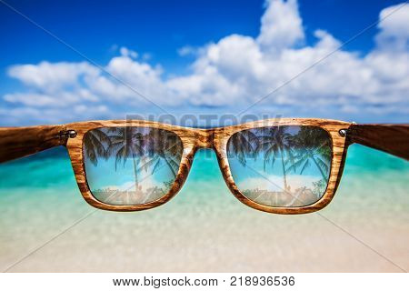 View at tropical resort beach and sea through sunglasses