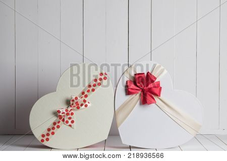 Heart shaped Valentines Day gift boxes on white wooden background