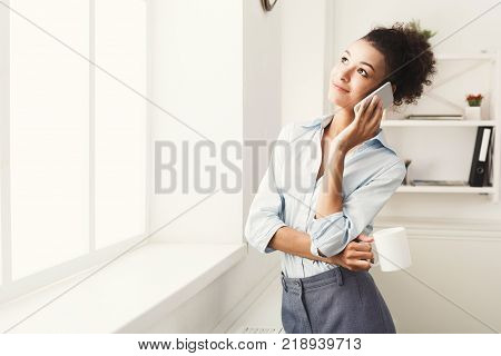 Happy smiling african-american business woman talking by phone near window at office workplace, drinking coffee. Communication, technology, success concept