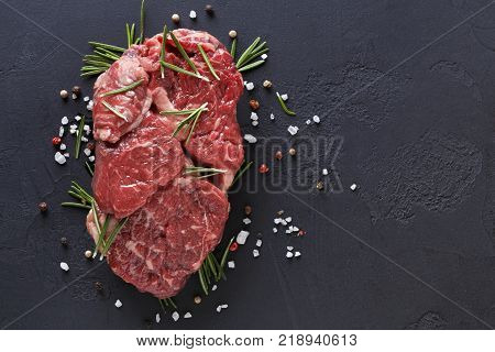 Raw rib eye steak with spices and vegetables. Ingredients for restaurant meal. Fresh meat, salt, rosemary, thyme, chilli, cherry tomatoes, garlic on black stone. Food background, copy space, top view