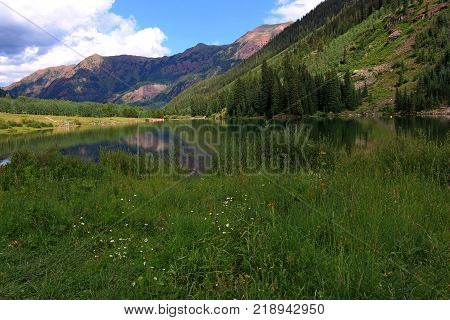 A reflective lake and two giant snow-striped mountaintops, named Maroon Peak and North Maroon Peak