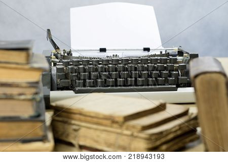 Typewriter And White Card Screwed Into The Machine. Wooden Table With A Typewriter.