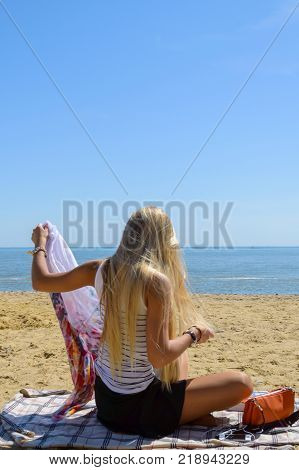 Enjoy life. Enjoying nature. Fashion portrait of the beauty girl staring on the sea. Gorgeous woman with blonde hair beach enjoying summer holiday.